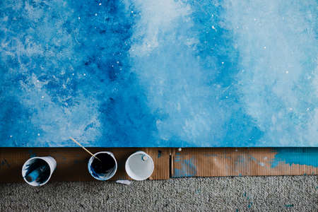arts and craft hobbies concept, blue and white acrylic painting with colors in plastic cups and mixed painting tools next to it while the work is in progress