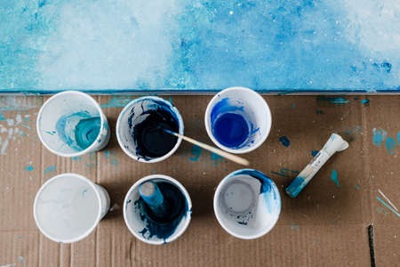 arts and craft hobbies concept, blue and white acrylic painting with colors in plastic cups and mixed painting tools next to it while the work is in progress Stock Photo