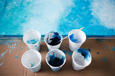 arts and craft hobbies concept, blue and white acrylic painting with colors in plastic cups and mixed painting tools next to it while the work is in progress Stock fotó