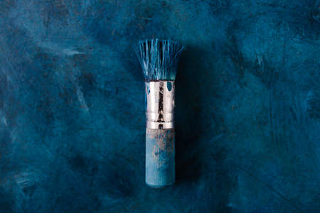 brush on top of finished work of an abstract textured painting or photography backdrop with blue and white tones acrylic paint