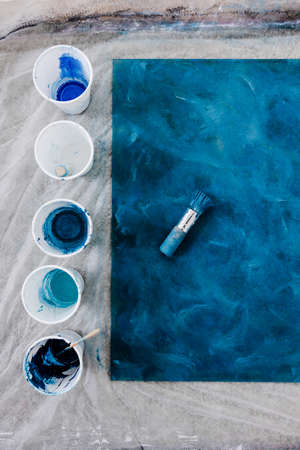 arts and craft hobbies concept, blue and black acrylic painting with colors in plastic cups and mixed painting tools next to it while the work is in progress