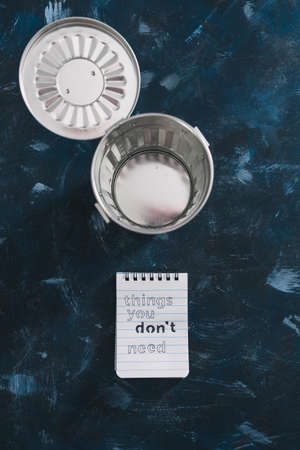 minimalism or self-improvement and introspection concept, notepad with texts Things you dont need with miniature trash can