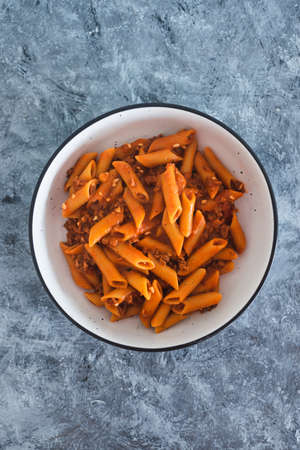 healthy plant-based food recipes concept, vegan penne pasta with red pesto and bean bolognaise sauce Stock Photo