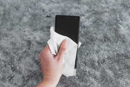 the new normal after covid-19 and concet of sanitizing surfaces, hand cleaning smartphone with disinfectant wipe to flatten the curve and prevent viruses and bacteria