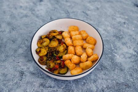 healthy plant-based food recipes concept, sauteed mediterranean vegetables with soy sauce and wir fried potato royals