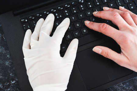 staying safe after the covid-19 virus pandemic outbreak, hand typing on shared computer keyboard at work wearing disposable glove to avoid contact with potentially infected surfaces and other hand without glove