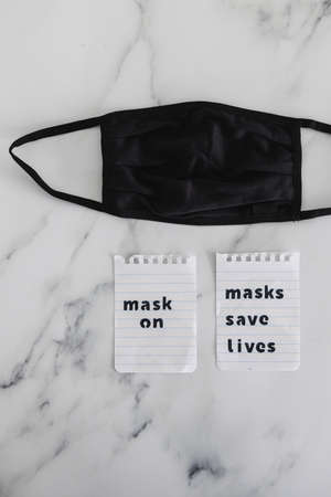 protection against the covid-19 virus outbreak and flattening the curve, reusable fabric face mask with text Masks save lives next to it
