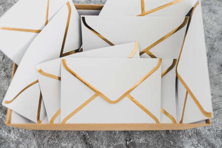 concept of inbox organisation and clean-up, group of envelopes inside box metaphor of email inbox Stock Photo