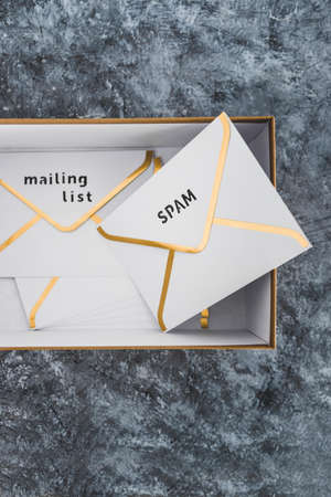 concept of inbox organisation and clean-up, group of envelopes inside box metaphor of email inbox and some marked as spam or mailing list content