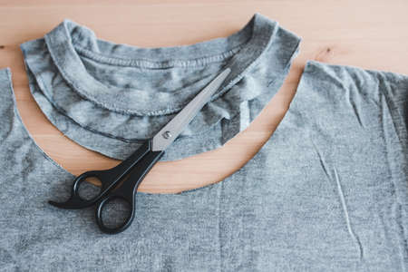 fashion diy and upcycling old clothes concept, t-shirt with scissors to cut a new neckline