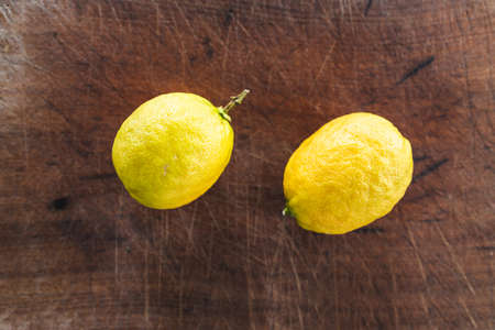simple food ingredients concept, couple of fresh lemons on cutting board on kitchen counter