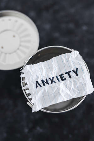 psychology and mental health concept, scrunched up memo with text Anxiety with garbage bin