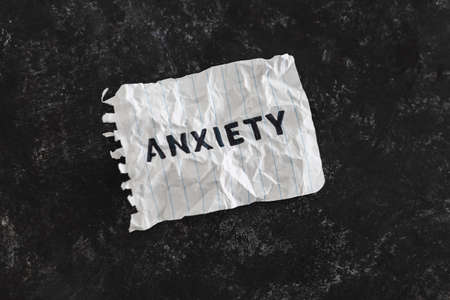 psychology and mental health concept, memo with text Anxiety scrunched up on black background