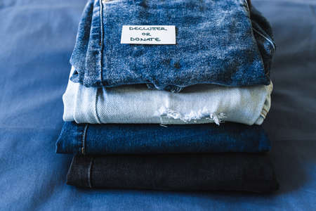 tidying up and organizing your wardrobe, Declutter and donate label on different jeans in various denim colors