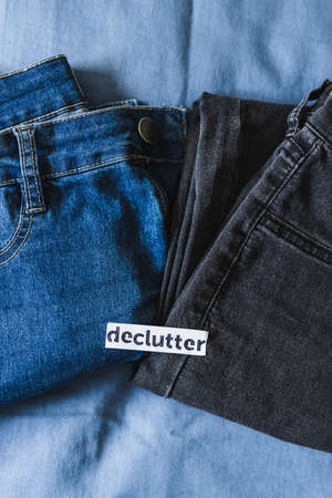 tidying up and organizing your wardrobe, Declutter label on different jeans in various denim colors Archivio Fotografico