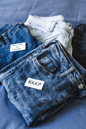 tidying up and organizing your wardrobe, Keep vs Declutter label on different jeans in various denim colors