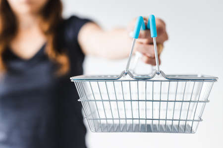 marketing and shopping concept, woman holding shopping cart towards the camera shot at shallow depth of field