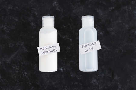 concept of imitations and unfair competition, couple of body lotion bottles with Original vs Dupe product labels Stock Photo