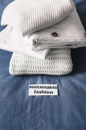 ethical brands and fair trade concept, pile of clothing with Sustainable Fashion label