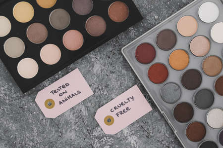 cruelty free vs animal tested cosmetics concept, eyeshadow palettes with text on labels Banque d'images