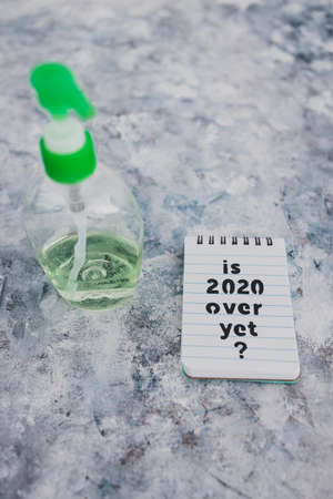 life after the covid-19 virus pandemic conceptual image, memo with text Is 2020 over yet next to hand sanitizer bottle