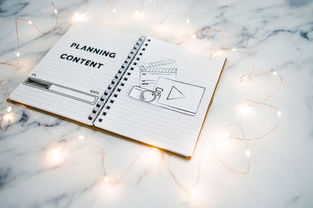 planning content for social media conceptual image, notebook with photo and video icon next to text and progress bar loading surrounded by fairy lights Foto de archivo