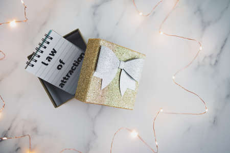 law of attraction conceptual image, text on notepad inside of present box surrounded by fairy lights