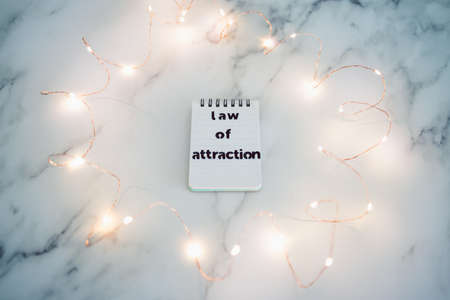 law of attraction conceptual image, text on notepad surrounded by fairy lights