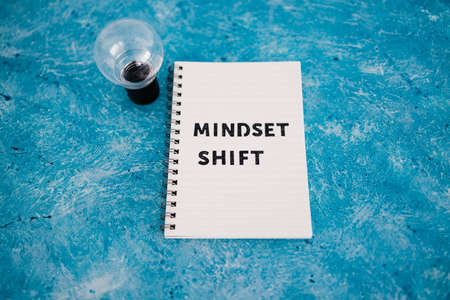 positivity and law of attraction conceptual image, notepad with Mindset Shift text with light bulb next to it Imagens