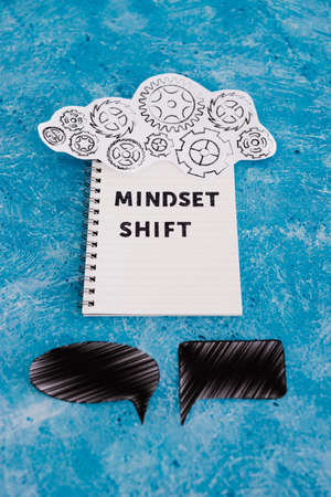 positivity and law of attraction conceptual image, notepad with Mindset Shift text with different thought bubbles and gearwheel mechanism next to it Imagens