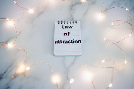 law of attraction conceptual image, text on notepad surrounded by fairy lights Banque d'images