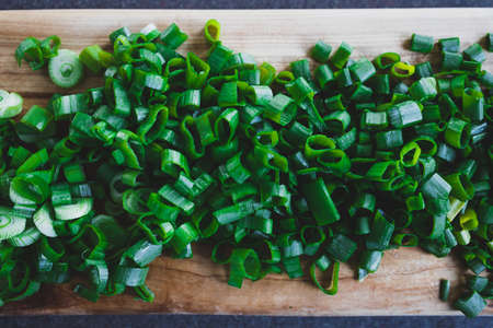 simple food ingredients concept, fresh spring onion getting chopped on cuttin boards