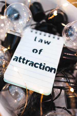 law of attraction and positive mindset conceptual image, box as metaphor of the mind with Law Of Attraction notepad on top of plenty of idea light bulbs surrounded by fairy lights