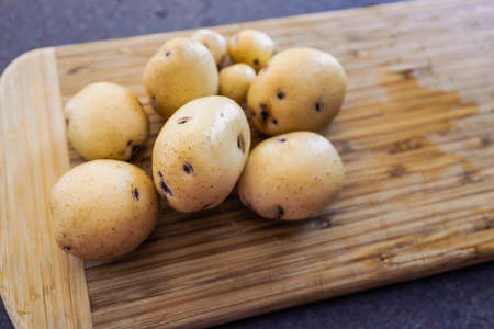 simple food ingredients concept, baby potatoes on cutting board Stock Photo