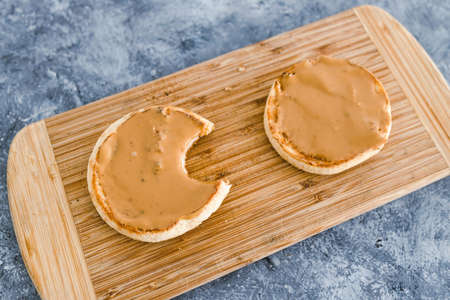 healthy plant-based food recipes concept, English muffins with smooth peanut butter topping on cutting board
