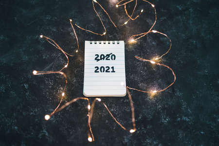 festive fairy lights with text 2020 crossed out and 2021 underneath, concept of facing the challenges caused by the outbreak of the covid-19 virus