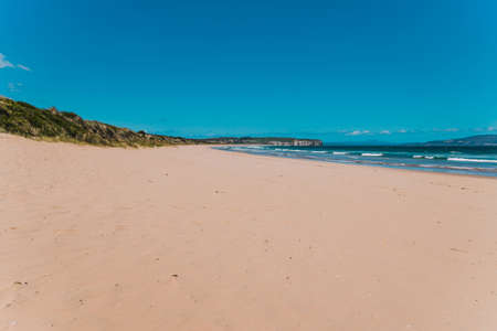 pristine wild landscape at Clifton Beach in South Hobart in Tasmania, Australia with wavy blue ocean and golden sand next to a rugged coastline