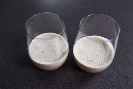 couple of espresso martinis in wine glasses on kitchen counter Stock Photo