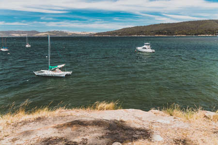 SNUG BEACH, AUSTRALIA - December 26th, 2020: pristine wild landscape at Snug Beach in South Hobart in Tasmania, Australia with wavy blue ocean and sailing boats Editorial