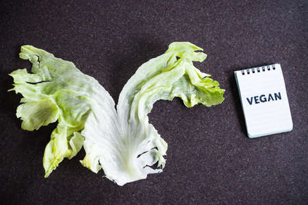 plant-based diet and healthy lifestyle concept, piece of iceberg lettuce in a V shape next to notepad with Vegan text on it
