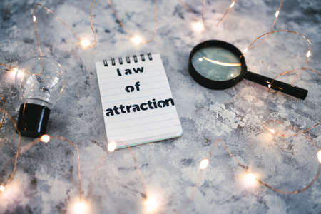 law of attraction notepad with text next to light bulb and magnifying glass symbol of introspection and mindset shift surrounded by fairy lights