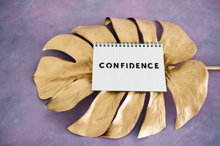 psychology and attitude concept, Confidence notepad on top of golden leaf on pink background