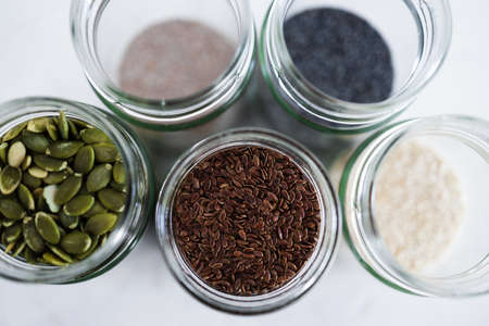simple food ingredients concept, seed jars with sesame poppy pupmkin chia and flax seeds as important nutrient sources for nutrition shot on white background Foto de archivo