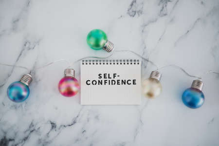 psychology and positive attitude concept, Self--confidence text on notepad surrounded by light bulbs on marble desk