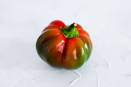 small bell pepper ripening from green to red isolated on white background, simple food ingredients concept