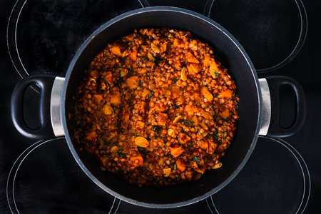vegan pumpkin lentil and mushroom curry in pot on the stove, healthy plant-based food recipes