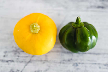 close up of small green bell pepper and squash on wooden surface, simple food ingredients concept