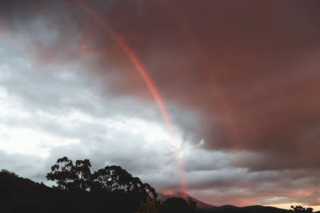 pink sunrise with rainbow in front of the colorful clouds with mountain tops and eucalyptus gum trees featuring Mount Wellignton in Tasmania, Australia