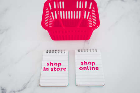 competition and retail industry conceptual image, pink shopping baskets with shop in store vs shop online texts on notepads
