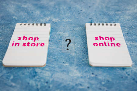 competition and retail industry conceptual image, shop in store vs shop online texts on notepads with question mark in between them